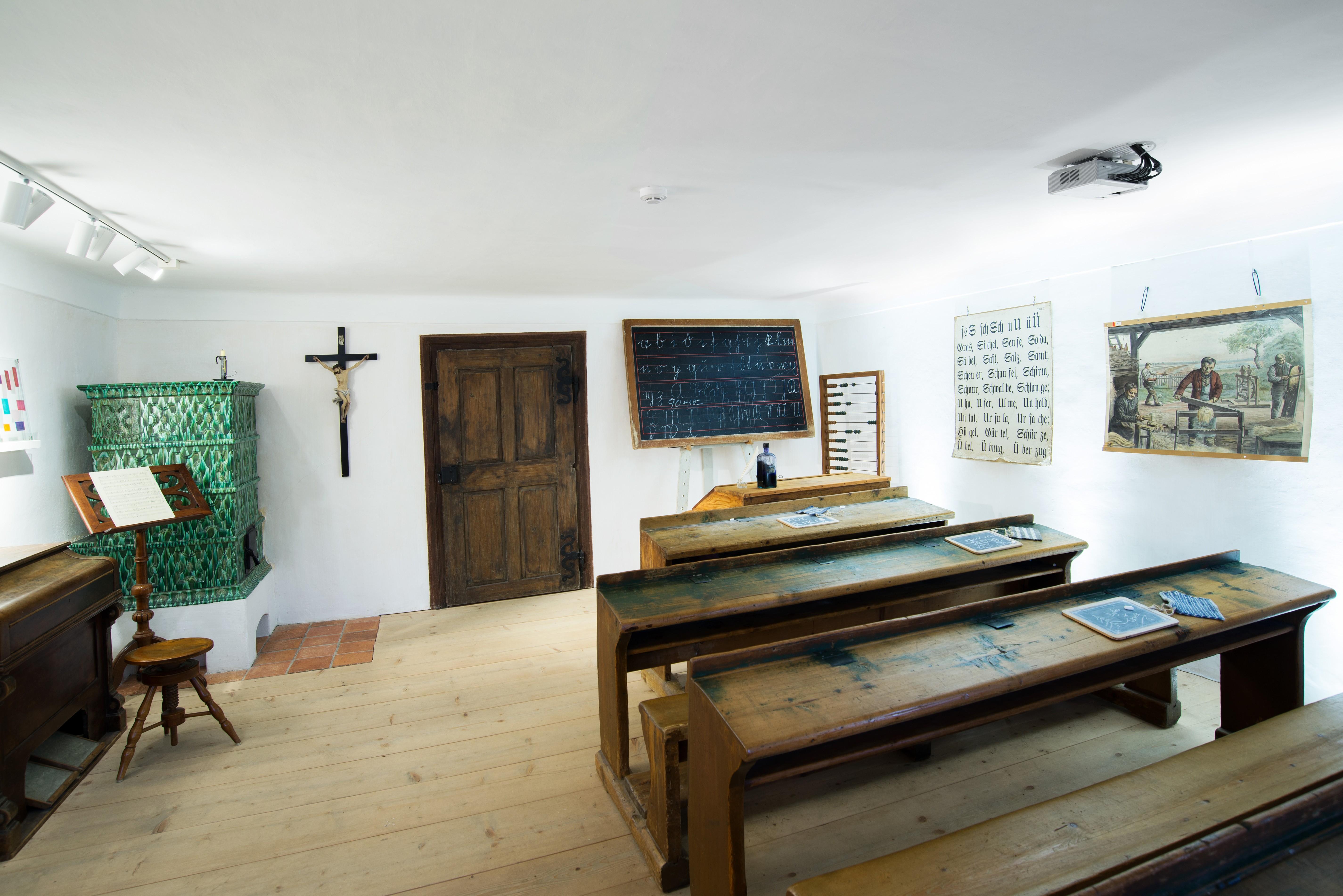La vecchia aula scolastica nel museo di Arnsdorf, con i banchi di legno, la cattedra il grande crocifisso alla parete e la stufa di maiolica verde