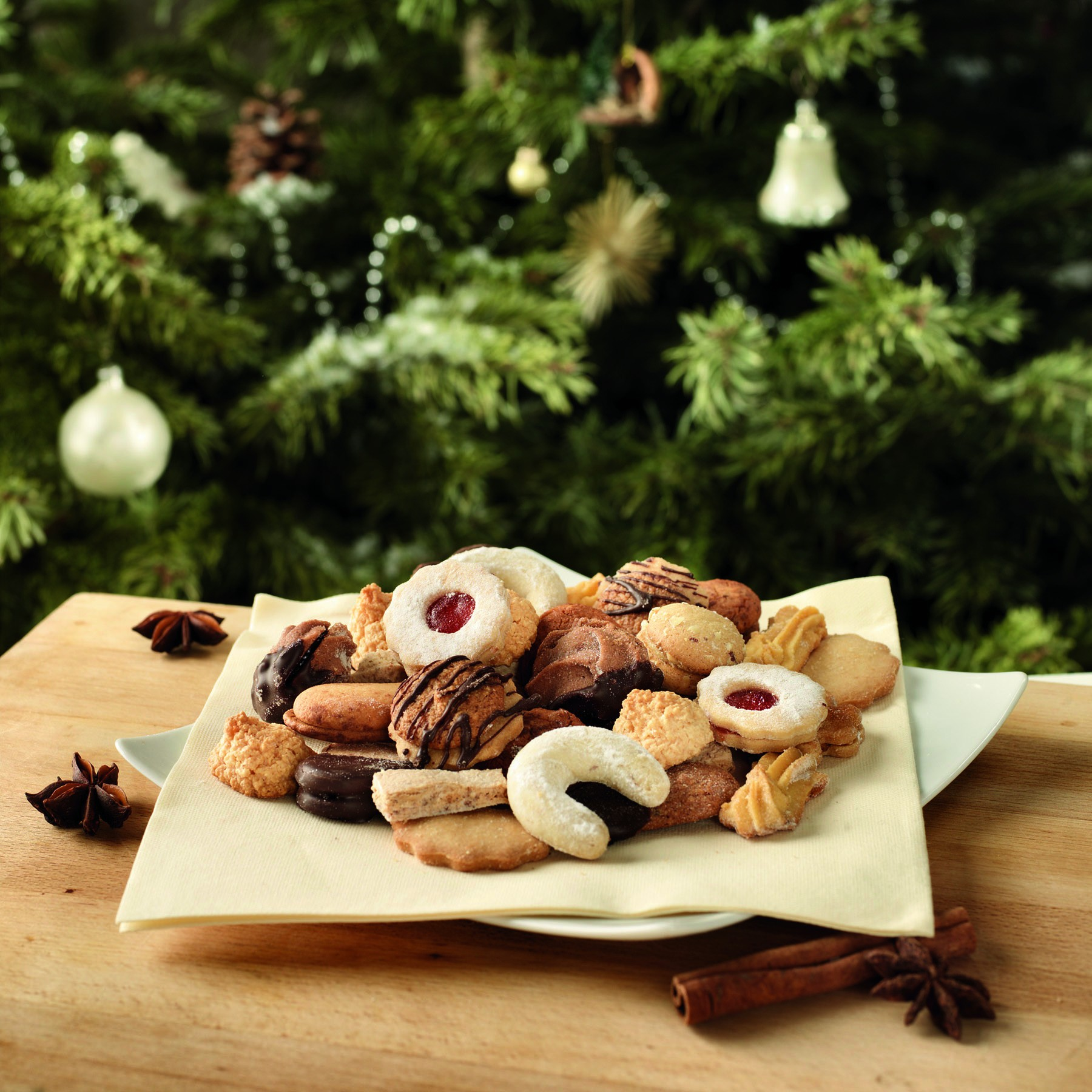 Piatto di biscottini natalizi sul tavolo davanti all'albero di Natale