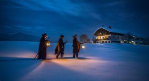 """Tre scampanatori """"Anglöckler"""" camminano verso una casa nella neve alla luce di lanterne"""