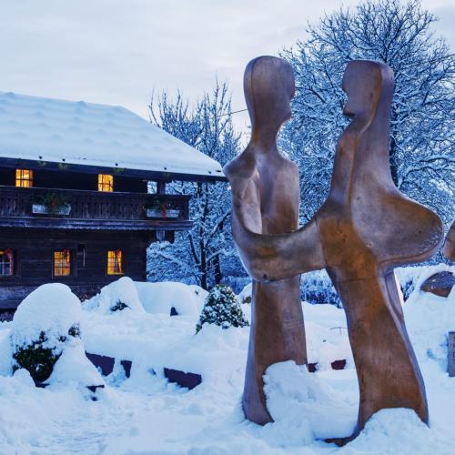 Scultura in legno all'aperto sotto la neve, con due figure che si fondono in un braccio