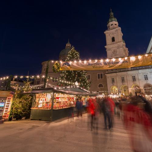 Mercatino d'Avvento a Salisburgo con luci, neve, bancarelle ecampanile della chiesa di notte