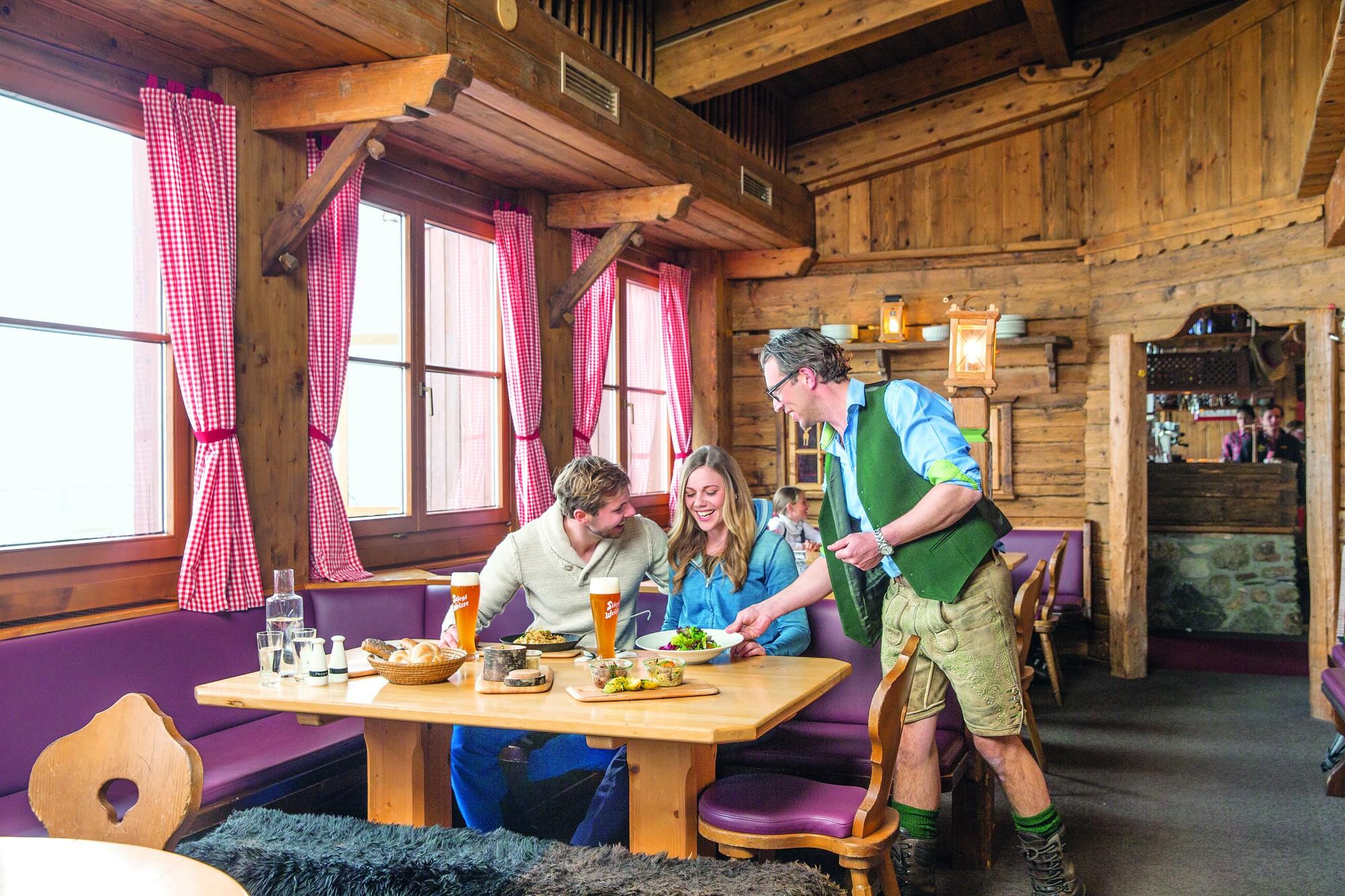 Coppia seduta alla finestra di un tipico locale, ambiene in legno, cameriere in costume tradizionale