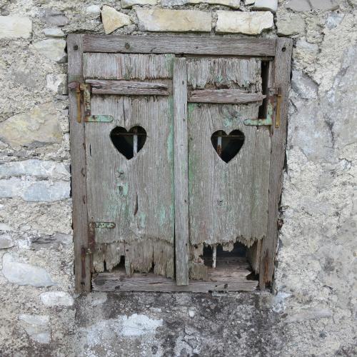 Vecchia finestra di legno con due aperture a cuoricino
