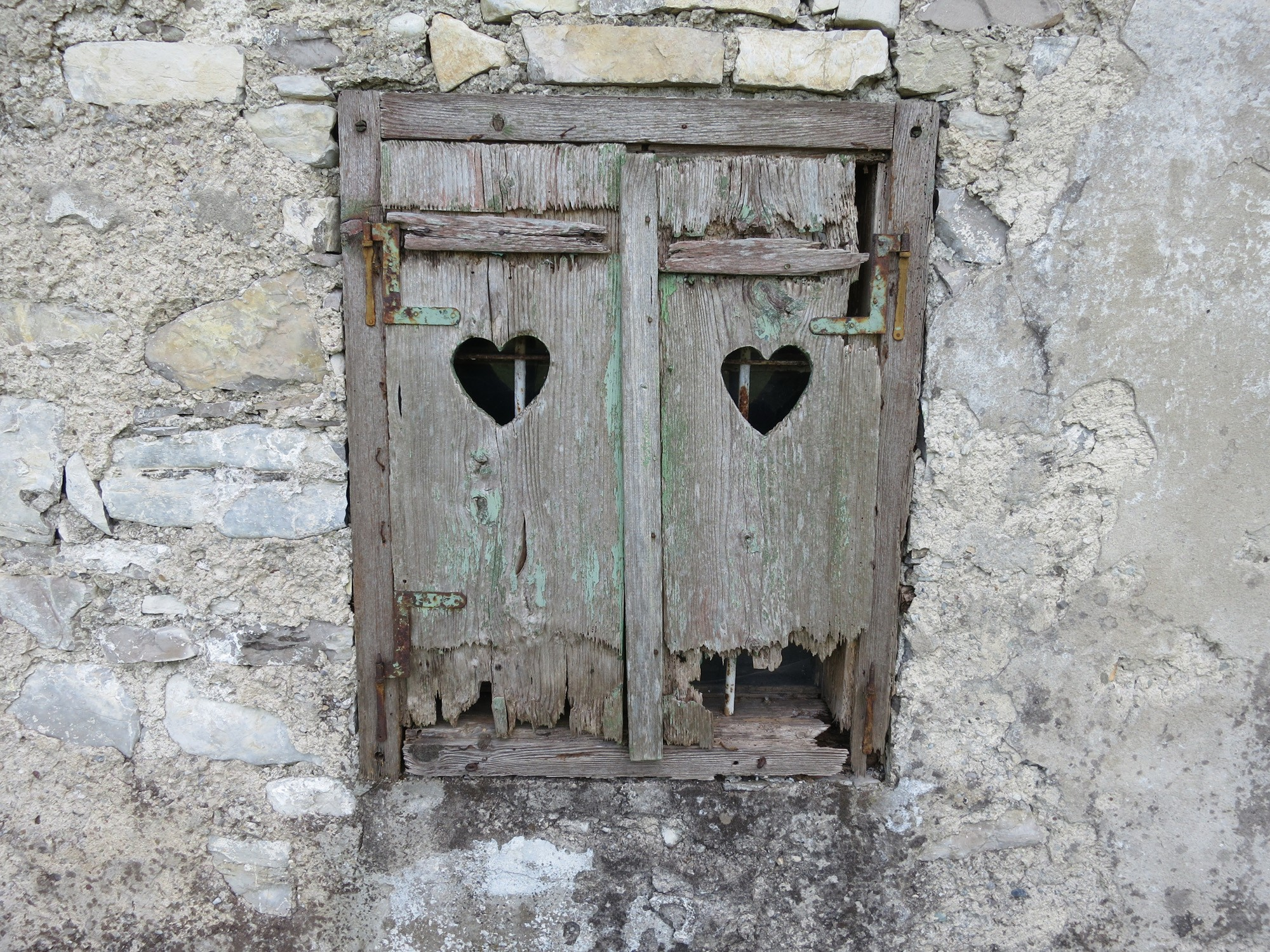 Kaputte Holzläden eines Fensters mit Herzen