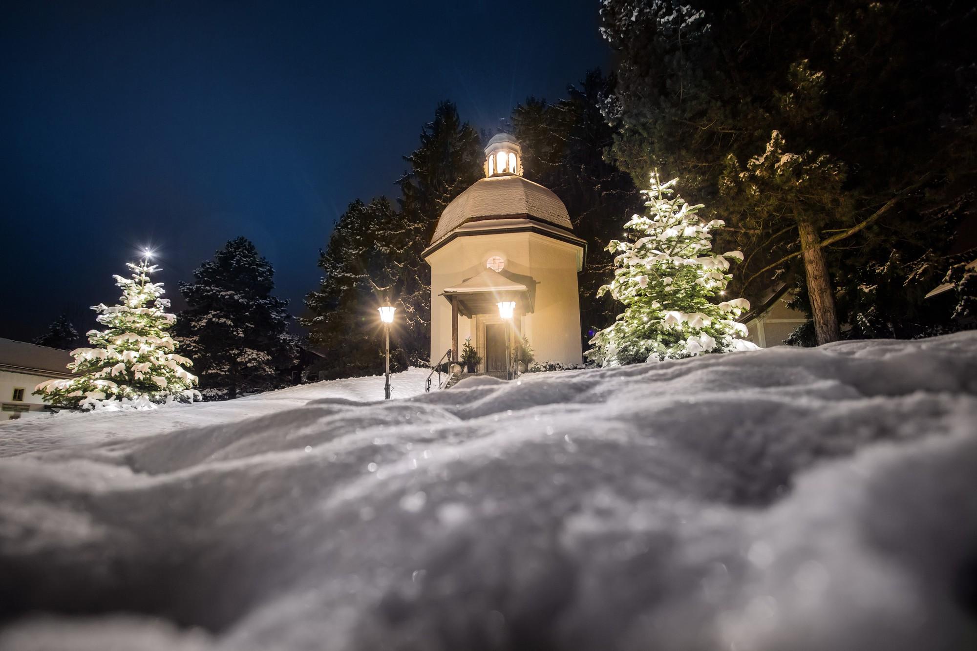 La cappella Stille Nacht a Oberndorf in mezzo alla neve con le luci di 2 lampioni